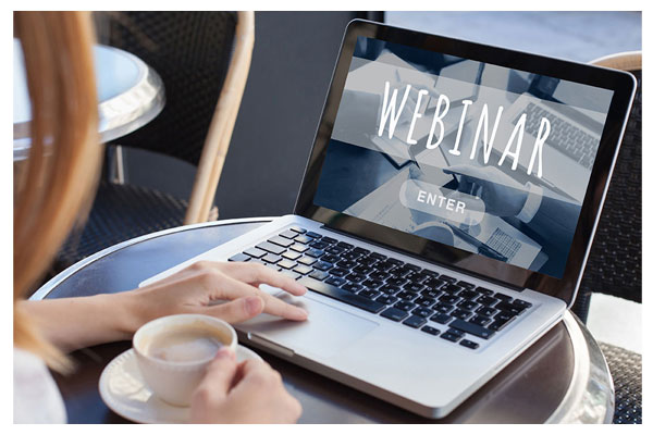 Woman having coffee on laptop with the word webinar displayed